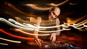 与耳机的秃头微笑的俱乐部DJ混合音乐 免版税库存图片