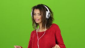 与耳机的美国黑人的女孩跳舞在绿色屏幕,特写镜头上 影视素材