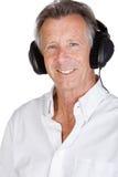 与耳机的英俊的高级男 免版税库存图片