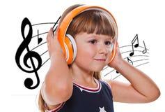 与耳机的逗人喜爱的愉快的小女孩听的音乐 图库摄影