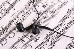 与耳机的音乐纸张 免版税库存照片