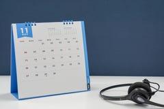 与耳机的11月日历在办公室 图库摄影