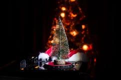 与耳机的Dj搅拌器在黑暗的夜总会背景与圣诞树除夕 关闭新年元素或symb看法  库存图片