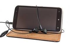 与耳机的Smartphone 免版税库存照片
