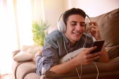 与耳机说谎的面孔的青少年的观看的多媒体下来在couc 免版税库存图片