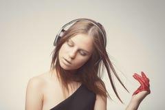 与耳机,佩带的红色手套,接近的眼睛的时尚俏丽的女孩听的音乐和采取与歌曲的乐趣 库存照片