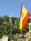 与耶稣基督雕象的西班牙旗子在背景 免版税库存图片
