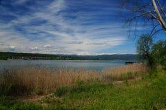 与耸立在湖的白色山的地中海风景 免版税库存照片