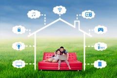 与聪明的房子技术系统的愉快的家庭 库存照片