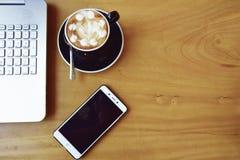 与聪明的电话膝上型计算机和咖啡杯老鼠notepa的办公室材料 免版税库存照片