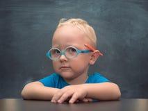 与聪明的神色的男婴佩带的玻璃 免版税图库摄影