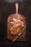 与肉叉子的优秀烤或烤丁骨牛排在黑暗的铁锈金属背景的年迈的木切板 免版税库存照片