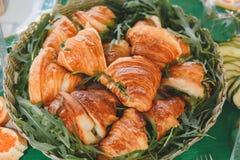与肉和乳酪装填的开胃在一个被编织的土气篮子的新月形面包和芝麻菜 关闭 库存图片
