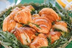 与肉和乳酪装填的开胃在一个被编织的土气篮子的新月形面包和芝麻菜 库存图片
