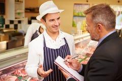 与肉店店主的银行经理会议  免版税库存图片