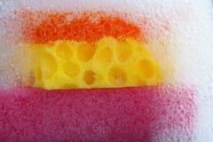 与肥皂泡沫的清洁海绵在上面 五颜六色的紫罗兰色橙黄色宏观视图泡影suds,灰色黑背景 库存图片