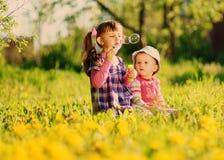 与肥皂泡的两个女孩戏剧在春天 免版税库存照片