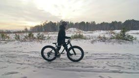 与肥胖自行车的专业极端运动员骑自行车的人步行在户外 走在冬天雪森林人的骑自行车者去 股票录像