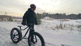 与肥胖自行车的专业极端运动员骑自行车的人步行在户外 走在冬天雪森林人的骑自行车者去 股票视频