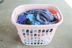 与肮脏的洗衣店的桃红色篮子在地板上 库存图片