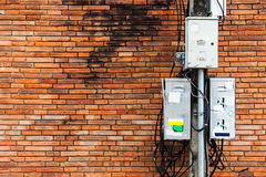 与肮脏的电子控制箱和缆绳,砖的电杆 库存照片