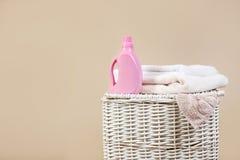 与肮脏的衣裳、清洁毛巾和洗涤剂的柳条洗衣篮在颜色背景 免版税库存照片