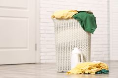 与肮脏的衣裳的在地板上的洗衣篮和洗涤剂在屋子里 免版税图库摄影