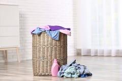 与肮脏的衣裳的在地板上的洗衣篮和洗涤剂在屋子里 免版税库存照片