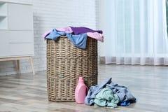 与肮脏的衣裳的在地板上的洗衣篮和洗涤剂 库存图片