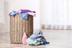 与肮脏的衣裳的柳条在户内地板上的洗衣篮和洗涤剂 免版税库存图片