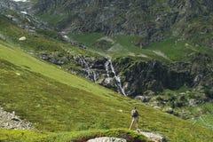 与背包的少妇旅行在山 免版税库存图片
