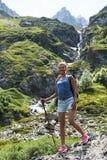 与背包的少妇旅行在山 库存照片