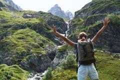 与背包的少妇旅行在山 免版税图库摄影