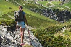 与背包的少妇旅行在山 免版税库存照片