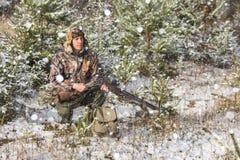 与背包的猎人和狩猎在冬天森林里开枪 库存图片