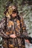 与背包的猎人和狩猎在冬天森林里开枪 免版税库存图片