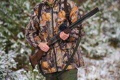 与背包的猎人和狩猎在冬天森林里开枪 图库摄影