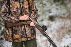 与背包的猎人和狩猎在冬天森林里开枪 库存照片