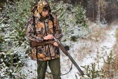 与背包的猎人和狩猎在冬天森林里开枪 免版税图库摄影