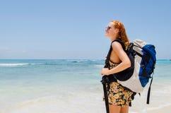 与背包的Gril在海滩 免版税图库摄影