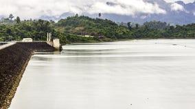 与背景山树和薄雾的美好的风景和在前面的一种河天空和自然吸引力在水坝泰国 免版税库存照片