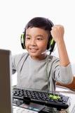 与胜利的亚洲孩子戏剧计算机游戏打手势 库存照片
