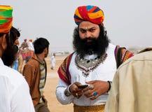 与胡子和头巾的严肃的Rajput在一个手机拨号 库存照片