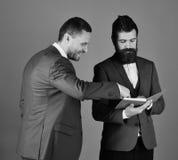与胡子的商人谈论调查笔记的事务 经典衣服的强壮男子谈论日程表 人与 免版税库存照片