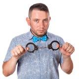 与胡子的成年男性在夏天衬衣的一个蓝色蝶形领结在被隔绝的警察手铐 免版税库存照片