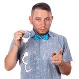 与胡子的成年男性在夏天衬衣的一个蓝色蝶形领结在被隔绝的警察手铐 库存图片