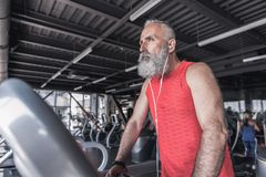 与胡子的时髦的男性是做心脏在现代健身房 库存图片