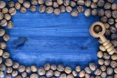 与胡桃钳的核桃在蓝色木桌上 免版税库存图片