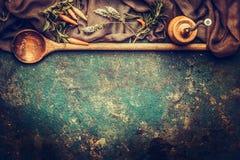 与胡椒磨、木烹调匙子和新鲜的调味料的食物背景在黑暗的土气葡萄酒背景 库存照片