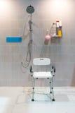 与胳膊和后面的被填塞的阵雨椅子在有明亮的t的卫生间里 免版税库存照片